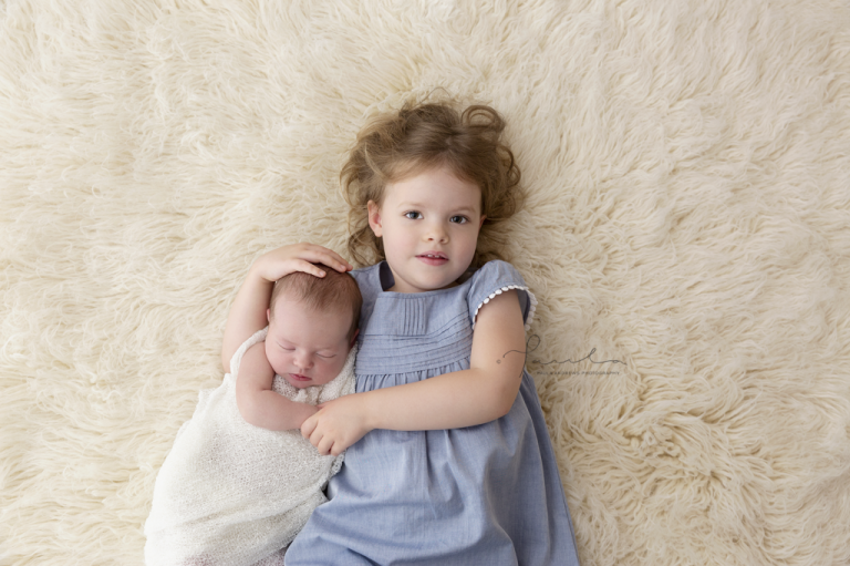 Big sister lying on back with her arms around her newborn baby sister, Paula Andrews Photography, Melbourne
