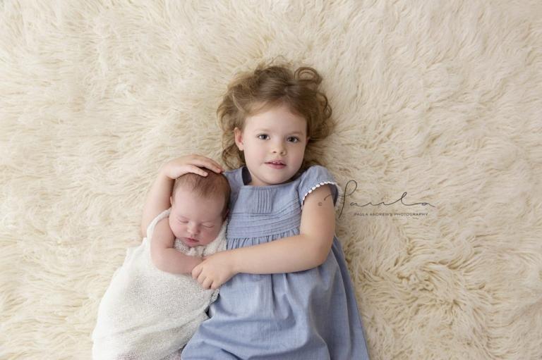 Sister hugging newborn sister