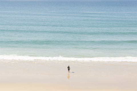 Surfer entering water at Noosa Heads in the Sunshine Coast
